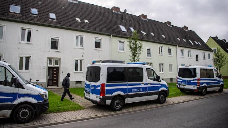 Polizei-Autos vor Wohnhäusern bei einer Razzia. Foto von der dpa, honorarfrei
