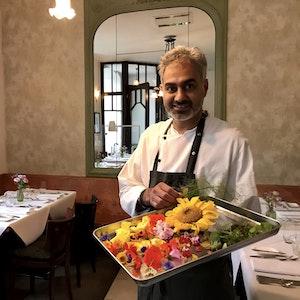 Jaspreet Dhaliwal-Wilmes steht mit einem Tablett Blüten in seinem Restaurant.