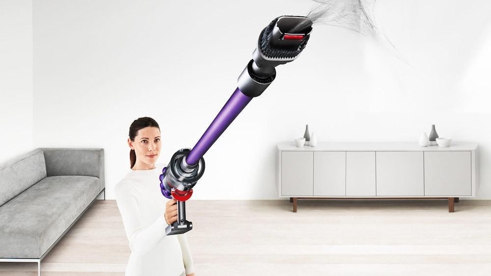 Eine Frau saugt die Wohnung mit einem kabellosen Dyson V11 Absolute Extra Pro Staubsauger.