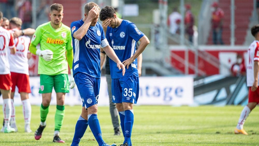 Simon Terodde (l.) und Marcin Kaminski von Schalke verlassen nach dem Spiel in Regensburg den Platz.