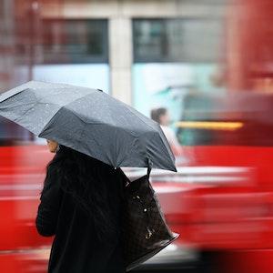 Eine Frau steht am Morgen (4. Juni 2020) mit einem Regenschirm an einer Straßenbahnhaltestelle. Regen bestimmt kurz vor dem Wochenende das Wetter in Nordrhein-Westfalen.