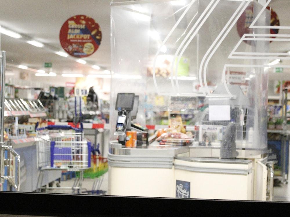 Absperrband der Polizei um den Kassenbereich in einem Supermarkt.