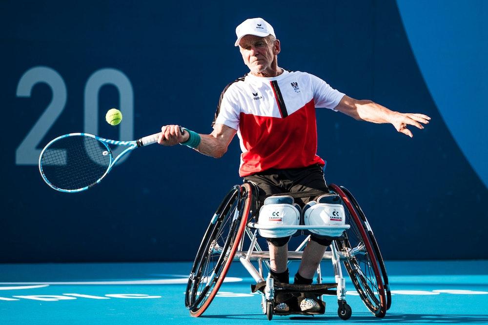 Martin Legner schlägt sitzend mit dem Tennisschläger gegen den Ball.