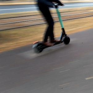 Ein Mann fährt mit einem E-Tretroller auf einem vom Gehweg abgetrennten Radweg neben Straßenbahnschienen durch die Stadt.