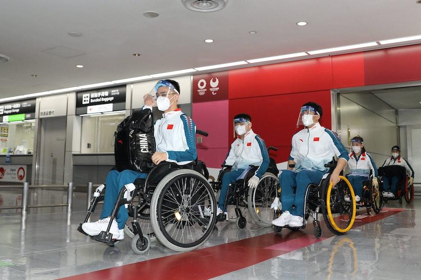 Chinesische Sportler in Rollstühlen mit Mundschutz und Plastikschutz.