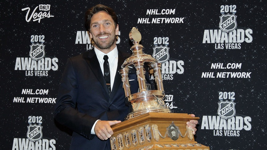 Henrik Lundqvist posiert mit der Vezina Trophy für den besten Keeper der NHL.