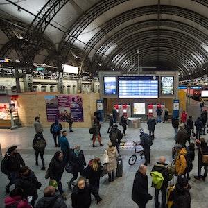Zugreisende stehen im Dezember 2018 im Dresdner Hauptbahnhof vor einer Anzeigetafel.