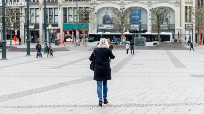 Eine Frau geht über einen großen Platz.
