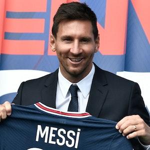 Lionel Messi posiert mit seinem neuen Trikot von Paris Saint-Germain.