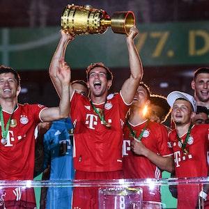 Leon Goretzka hält den DFB-Pokal mit seinen Händen in den Nachthimmel, neben ihm feiert Robert Lewandowski.