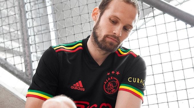 Ein Spieler sitzt im neuen schwarzen Trikot von Ajax auf einer Treppe und zieht sich die Stutzen zurecht.