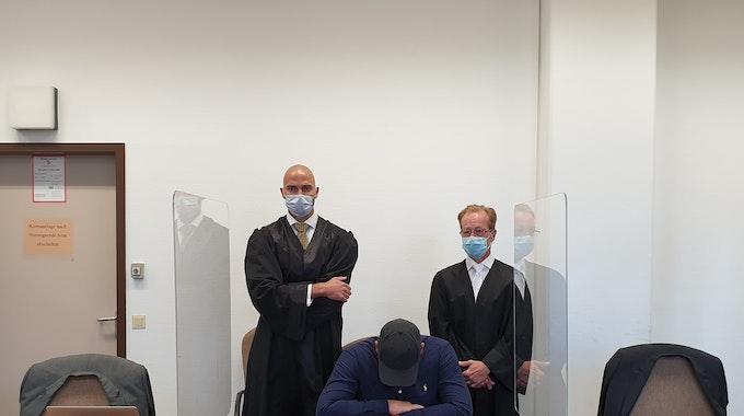 Das Hells Angels-Mitglied sitzt auf der Anklagebank, hinter ihm stehen seine beiden Anwälte.