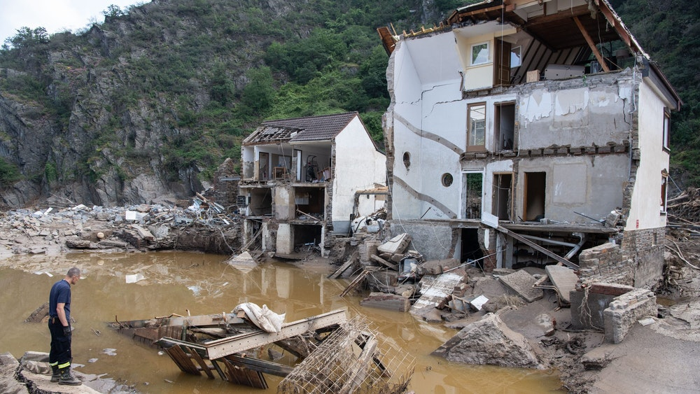 Ein Feuerwehrmann steht im Dorf Mayschoß vor einem völlig zerstörten Haus. Der Klimawandel erhöht laut einer Studie die Wahrscheinlichkeit extremer Regenfälle und damit von Hochwasserkatastrophen, wie sie im Juli in Rheinland-Pfalz und Nordrhein-Westfalen vielen Menschen das Leben gekostet hat.
