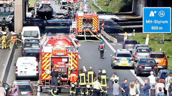 ARCHIV - 17.09.2020, Nordrhein-Westfalen, Mülheim: Feuerwehrleute stehen an dem ausgebrannten Tanklaster auf der A40. Der mit 35 000 Litern Kraftstoff beladene Tanklastzug hatte Feuer gefangen. Der LKW war nach einem Unfall mit einem Auto in Brand geraten (zu dpa: «Nach Brückenbrand an A40: Flüchtiger Tanklaster-Fahrer gefasst») Foto: Roland Weihrauch/dpa +++ dpa-Bildfunk +++