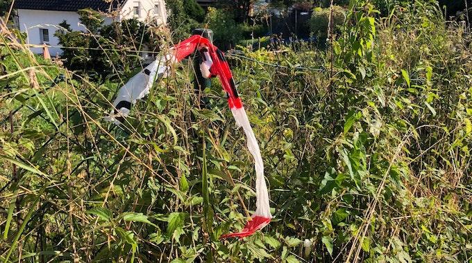 Ein rot-weißes Flatterband der Polizei hängt an einem Zaun.