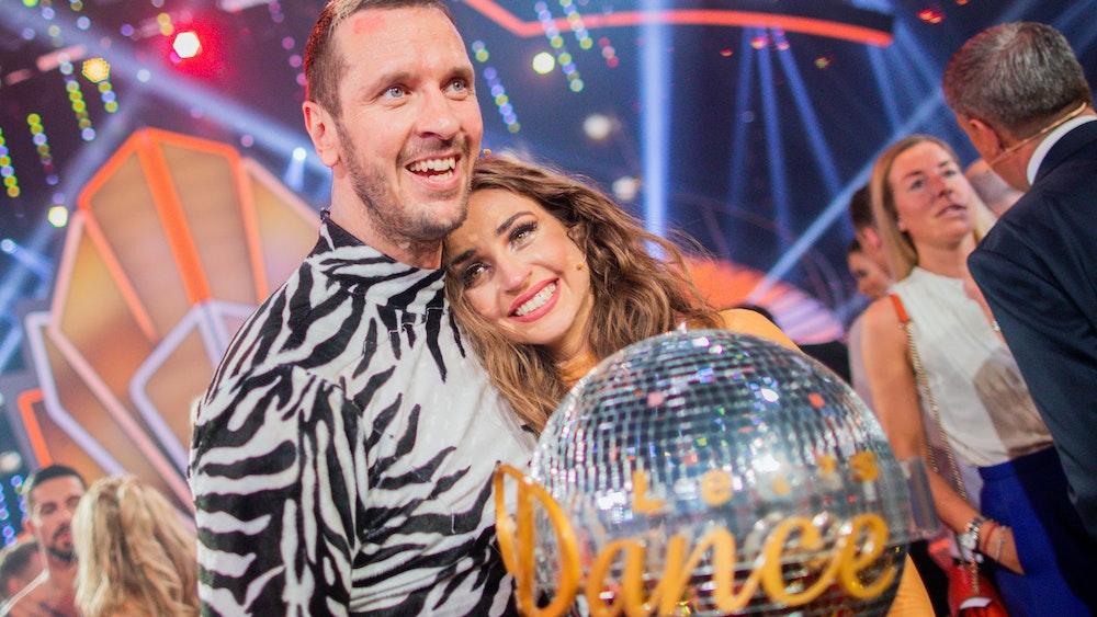 """Pascal Hens, ehemaliger Handballer, und Ekaterina Leonova, Profitänzerin, freuen sich 2019 in der RTL-Tanzshow """"Let's Dance"""" im Coloneum mit dem Pokal über den Sieg. Nun hat """"Ekat"""" Köln verlassen und einen neuen Job gefunden."""