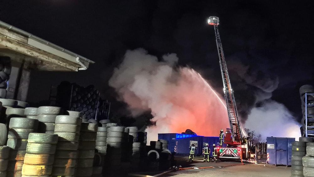 Feuerwehrleute löschen am 24.08.2021 von einer Drehleiter aus einen Brand in einem Reifenlager in Bochum.