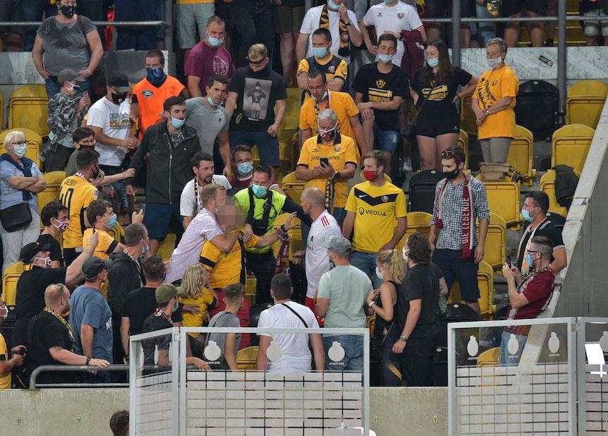 Toni Leistner steht auf der Tribüne inmitten von Dresden-Fans und baut sich vor einem Fan auf, der von einem anderen Fan zurückgehalten wird.