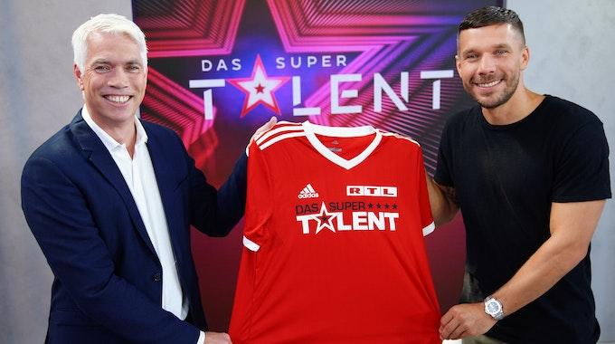 """Die Freude war groß bei RTL Ende Juni, als klar war, dass Fußball-Weltmeister Lukas Podolski (r., hier zusammen mit Henning Tewes, Geschäftsführer RTL) Juror beim """"Supertalent"""" 2021 sein soll. Nach Podolskis positivem Corona-Test ist der weitere Plan für die Produktion nun aber offen."""