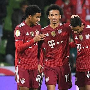 Bayerns Malik Tillmann (l) und Leroy Sane (M) freuen sich mit dem Torschützen zum 0:7 Jamal Musiala.
