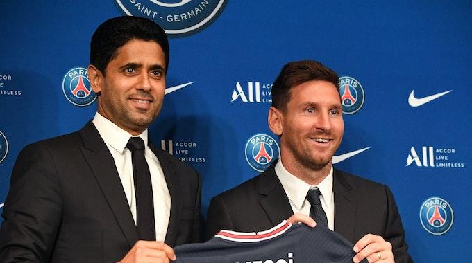 Lionel Messi und PSG-Präsident Nasser Al-Khelaifi halten ein PSG-Trikot hoch.