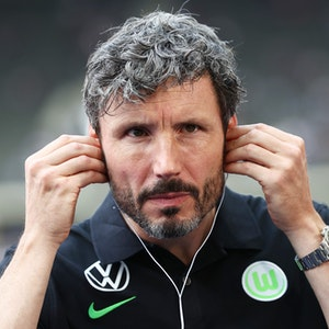 Wolfsburgs Trainer Mark van Bommel setzt Kopfhörer vor einem Interview auf.