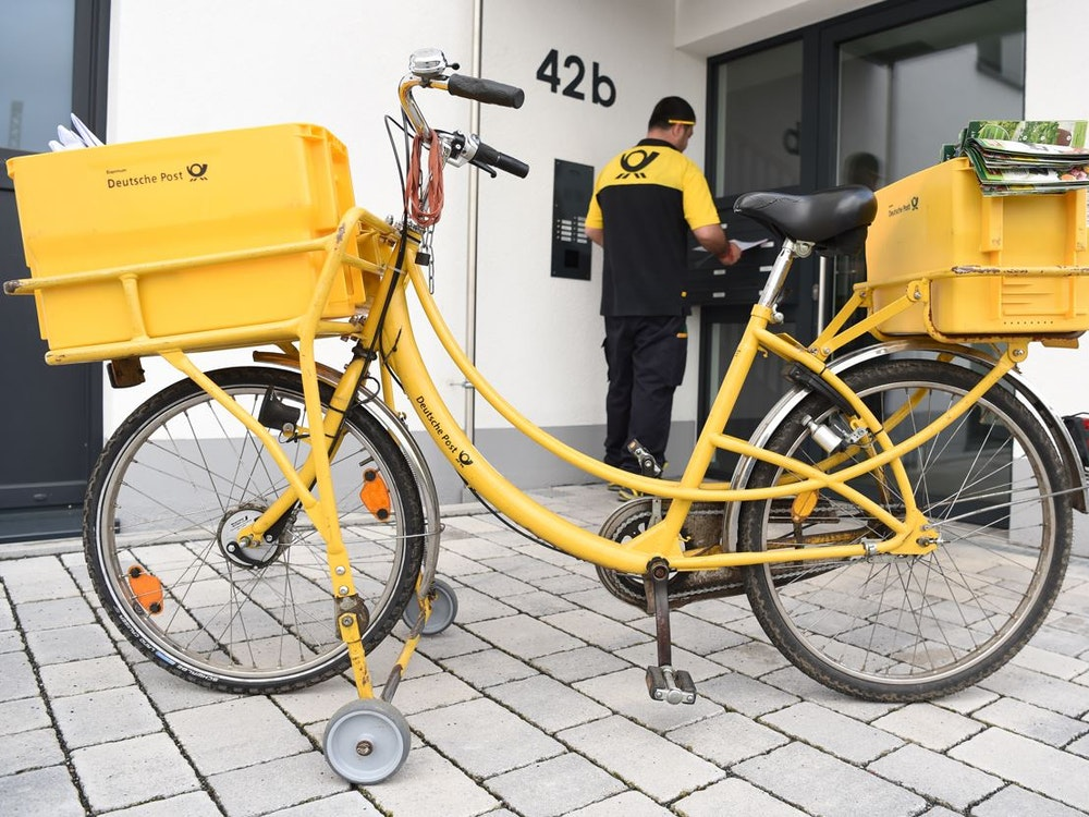 Postbote vor der Tür eines Hauses in Frankfurt am Main.