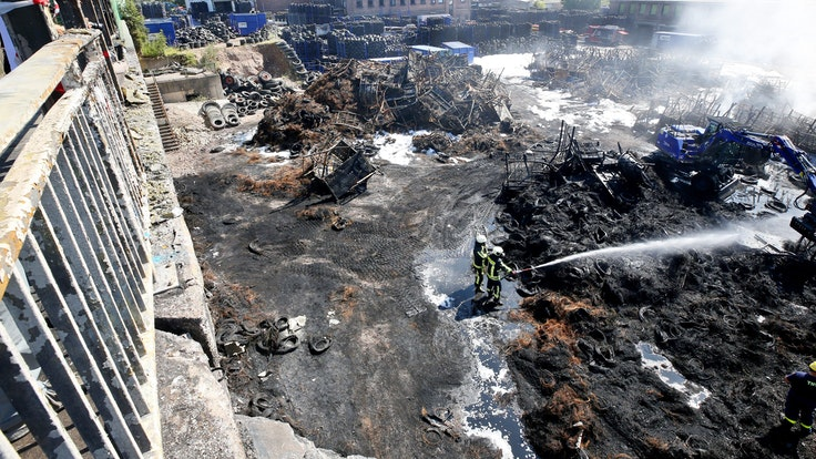 Nach dem Brand in einem Bochumer Reifenlager löschen Feuerwehrleute noch die letzten Brandnester.