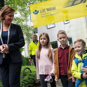 Yvonne Gebauer überquert mit Schülerinnen und Schülern der Grundschule Ferdinand-Lasalle die Straße vor der Schule.