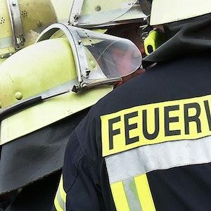 Der Schriftzug Feuerwehr steht während einer Rettungs-Übung an der Jacke eines Feuerwehrmannes, es handelt sich um ein Symbolfoto aus dem Jahr 2014