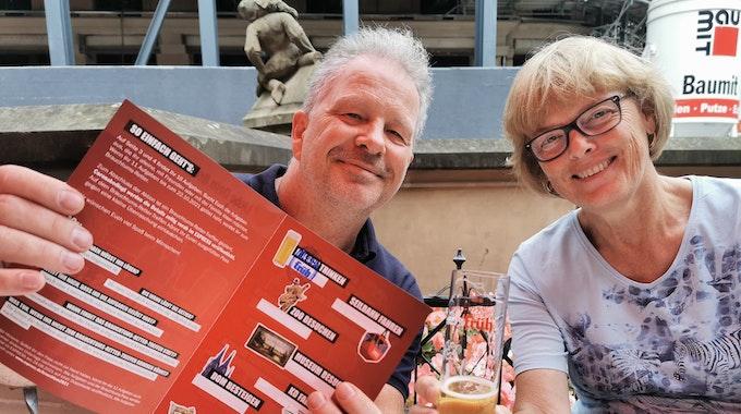 Hildegard aus Bornheim und EXPRESS-Reporter Oliver Meyer halten den Brauchtums-Pass in die Kamera und trinken Kölsch.