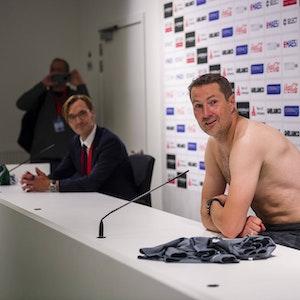 Brian Priske spricht mit nacktem Oberkörper auf der Pressekonferenz von Royal Antwerpen.