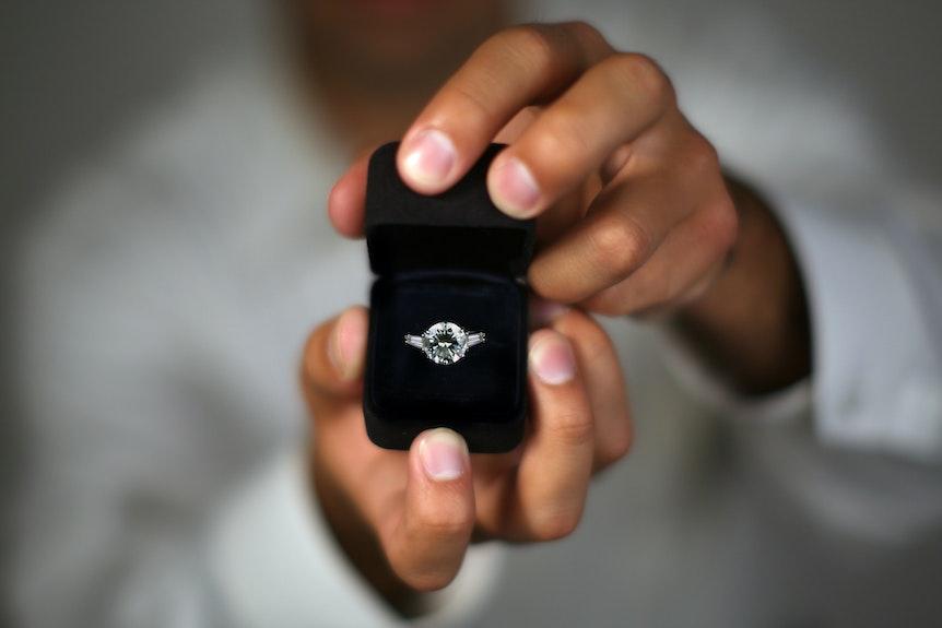 Ein Mann hält eine Ringschachtel mit einem Diamant-Ring in der Hand.