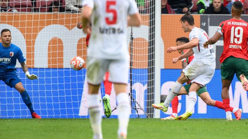 Iago (verdeckt) hebt den Ball im Spiel des FC Augsburg gegen Bayer Leverkusen über den eigenen Torwart.