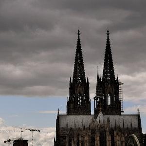 Der Kölner Dom mit seinen Turmspitzen kratzt an den dunklen Wolken.
