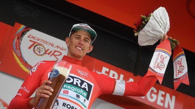 Nils Politt vom Team Bora-Hansgrohe jubelt nach der Etappe im Roten Trikot des Gesamtführenden auf dem Podium.
