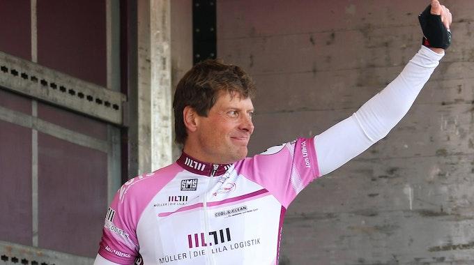 Jan Ullrich reckt am Rande eines Radrennens die Faust in die Luft.