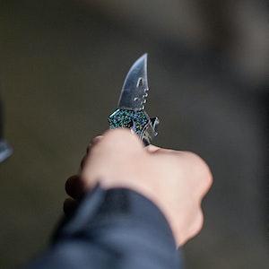Ein Polizist hält ein sichergestelltes Messer in der Hand.