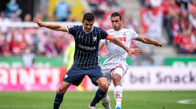 Kölns Ellyes Skhiri (r) und Bochums Anthony Losilla kämpfen um den Ball.