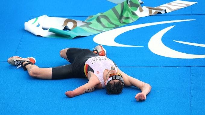 29.08.2021, Japan, Tokio: Paralympics: Triathlon, Finale, Männer, Odaiba Marine Park. Martin Schulz aus Deutschland liegt im Ziel auf dem Boden. Foto: Karl-Josef Hildenbrand/dpa +++ dpa-Bildfunk +++