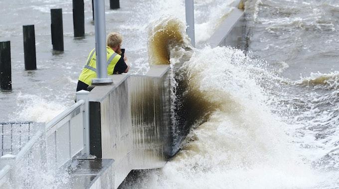Ein Arbeiter eines Versorgungsunternehmens fotografiert am 29.08.2021 die Wellen, die in Bay Saint Louis, Missouri, gegen eine Ufermauer im städtischen Jachthafen schlagen, während die äußeren Bänder des Hurrikans Ida eintreffen