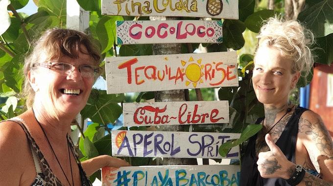 Goodbye Deutschland: Sonja Schröter steht mit ihrer Tochter Nena neben einer Palme, an welcher eine Cocktailkarte genagelt ist.