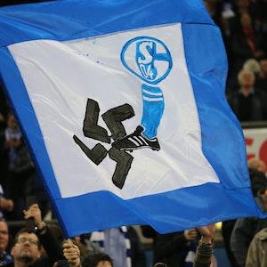 Auf einer Fahne ist ein Schalke-Wappen und ein Fuß zu sehen. Der Fuß zertritt ein Hakenkreuz.