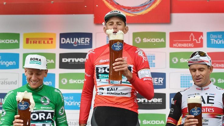Pascal Ackermann (l-r) aus Deutschland vom Team Bora-Hansgrohe im Grünen Trikot des Sprintbesten, Nils Politt aus Deutschland vom Team Bora-Hansgrohe im Roten Trikot des Gesamtführenden und der Norweger Alexander Kristoff vom UAE Team Emirates stehen nach der Etappe auf dem Podium.
