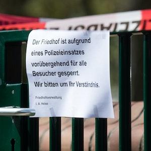 Ein Schild informiert über einen Polizeieinsatz auf einem Friedhof.
