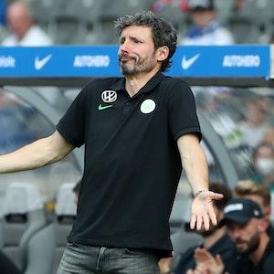 Mark van Bommel steht vor der Trainerbank und breitet fragend die Arme aus.