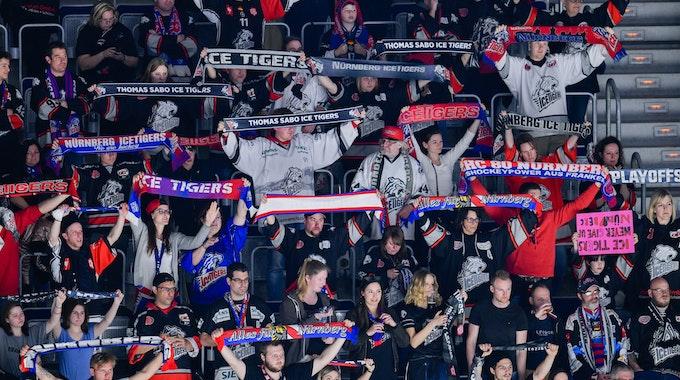 Fans der Nürnberg Ice Tigers halten ihre Schals in die Luft