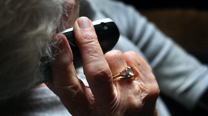 Eine ältere Frau, die einen wertvollen Ring am Finger trägt, telefoniert mit einem schnurlosen Festnetztelefon.