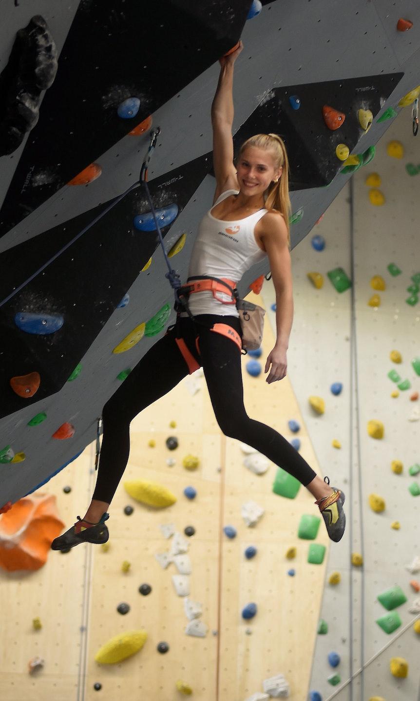 Kletterin Hannah Meul hängt mit einem breiten Grinsen an einem Arm an einem Griff in einer Kletterhalle.