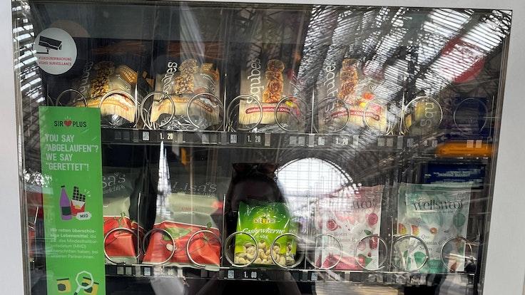 """Vegan, Bio, fast abgelaufen: Im """"Rettomat"""" gibt es zahlreiche Snacks für Reisende. Der Automat informiert außerdem über das Problem der Lebensmittelverschwendung."""